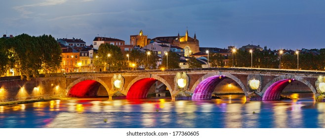 Evening panoramic view on illuminated Pont Neuf bridge in Toulouse, southern France