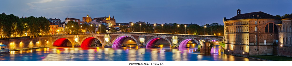 Evening panoramic view on illuminated Pont Neuf bridge and Hotel Dieu in Toulouse, southern France