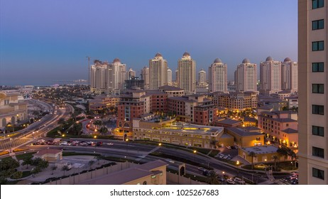 Evening at the Pearl-Qatar day to night timelapse from top. It is an artificial island in Qatar. Traffic on the road. View of the Marina and residential buildings in Porto Arabia in Doha, Qatar
