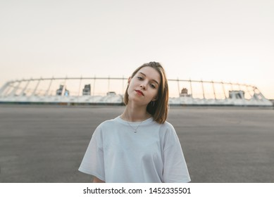 Evening portrait of an attractive girl with a serious face looking into the camera. A beautiful, well-dressed girl wearing casual clothing poses to the camera.