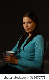 Evening portrait of young woman sitting in dark, drinking tea, looking at camera.