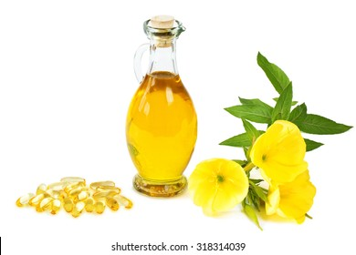 Evening primroses with gelatine capsules and oil bottle on white background
