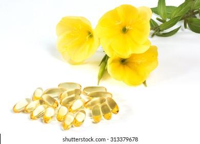 Evening primroses near yellow gelatin capsules on white background
