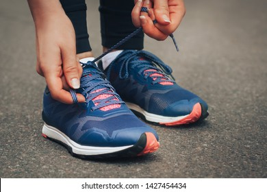 Evening run. Young lady running on a rural road during sunset in blue sneakers. Girl tying shoelaces before running