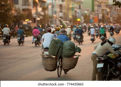 Evening rush hour with motorcycle riders in Asian city, soft focus on bicycle with two baskets. Motorbike, bicycles very popular form of transport in Asia. Traffic jam, city traffic concept