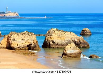 Evening sandy beach Praia dos Tres Castelos with rock formations, Portimao, Algarve, Portugal. Top view.