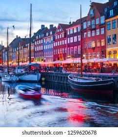Evening scene with boats moored by illuminated Nyhavn harbor embankment, Copenhagen, Denmark