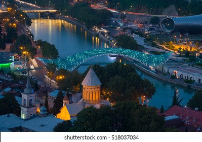 Evening scene in Tbilisi (Georgia) historical centrum. Illuminated  bridge of Peace and Kura river in the middle of composition.
