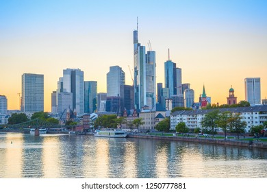 Evening scene with touristic boats on river by city embankment, modern architecture skyline against afterglow sky, Frankfurt am Main, Germany