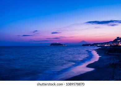 "Evening scenery of the coast of ""Shichirigahama"". Mount Fuji appears in silhouette at sunset. Kamakura city, Kanagawa, Japan."
