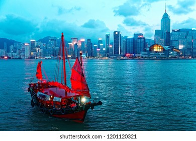Evening scenery of Hong Kong by Victoria Harbor with the landmark Convention & Exhibition Center among skyscrapers and an Aqua Luna tourist boat (Cheung Po Tsai) of Chinese junk style cruising at dusk