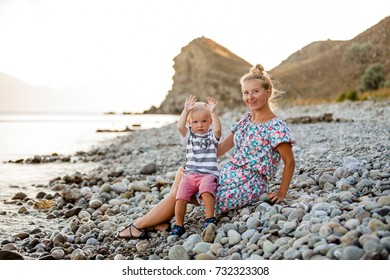 Evening, sea beach. The son sits on his mother's lap and eats fruit and berries