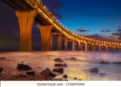 Evening seascape with a bridge. Road bridge with glowing lights on the background of the Bay and the evening sky. Evening motorway. Road bridge on high supports above the water.