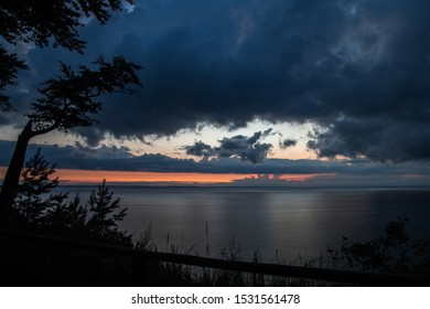 Evening seascape. Still sea in the evening. Sunset in the still ocean. Dark water, orange and pink sunset. Baltic beach landscape. Baltic sea shore in Poland. Dark clouds over the sea.