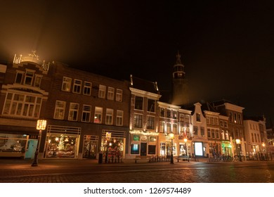 Evening shot of a street with old houses with bell gables. In the background the tower of the Sint-Janskerk with illuminated clock. Gouda, the Netherlands.