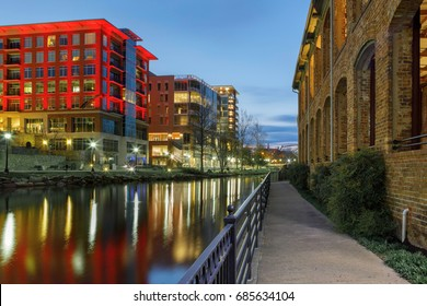 Evening sights along the Reedy Riverwalk in downtown Greenville, South Carolina as lights shine and reflect across the water.