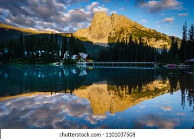 Evening sky and clouds light up with sunset colors; perfect reflections in the mirror smooth water of Emerald Lake, show off the lodge in Yoho National Park, Canada