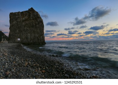 Evening sky, rock in the form of a sail, sea and clouds