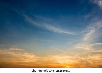Evening sky scene with golden light from the setting sun and blue-tinting filled with white cloud streaks