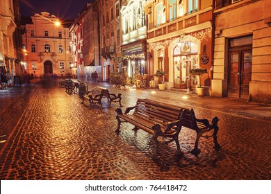 Evening street with benches and lanterns. Night European city