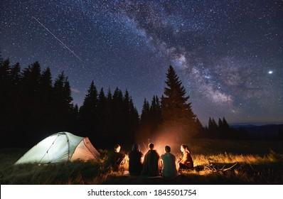 Abends Sommercampingplatz, Fichtenwald auf dem Hintergrund, Himmel mit fallenden Sternen und Milchweg. Gruppe von fünf Freunden, die zusammen um das Lagerfeuer in den Bergen sitzen und frische Luft in der Nähe des beleuchteten Zeltes genießen
