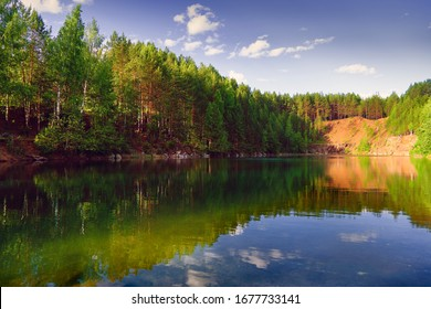 Evening summer landscape on the shore of a forest lake with clear transparent blue water.