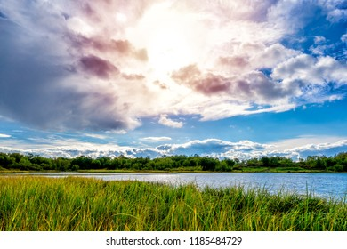 Evening sun behind clouds above the lake