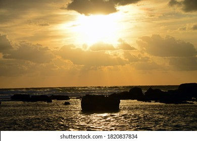 The evening sun bursting through clouds over sea and rocks. Artistic, silhouetted photo, shot against the light (contre-jour) from the nearby beach.