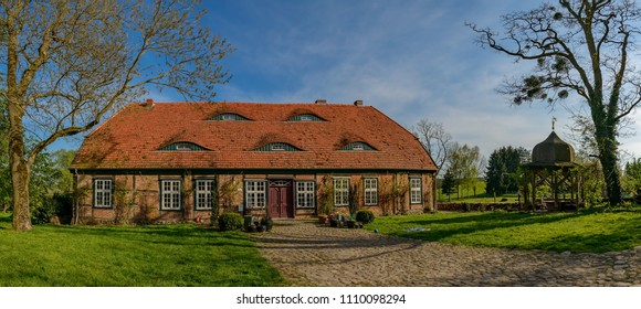 The evening sun covers the listed historical clergy house of Rambow in warm light - Panorama from 5 pictures