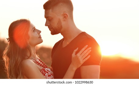 Evening sun illuminates young couple hugging on field. Love, friendship and family concept