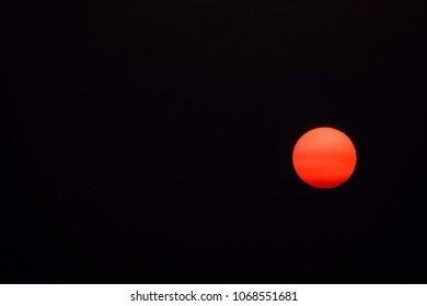 Evening sun, orange with atmospheric refraction, with three sunspots, low above the horizon in a dark sky, for themes of summer, perception, transition