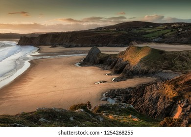 Evening sun over the river at Three Cliffs Bay and The Great Tor at Penmaen, Gower, Swansea, UK