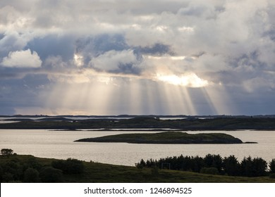 Evening sun rays over islands in Helgeland archipelago Norway.