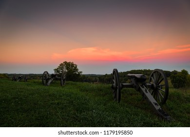 The evening sun setting on a trio of American Civil War cannons.
