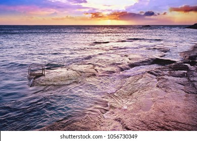 Evening sun in violet and gold in the sky over the Atlantic Ocean on Tenerife.The Atlantic shimmers in various shades of blue and violet, all the way to emerald green. rest and peace radiate the pic.