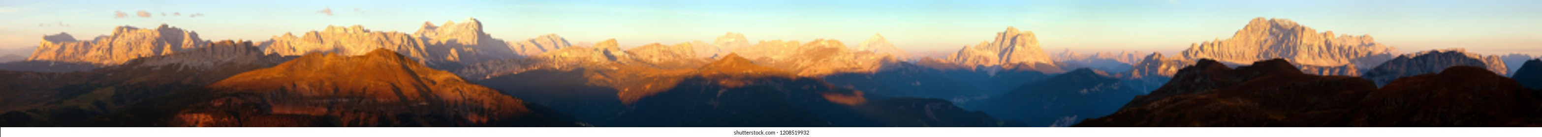 Evening sunset colored panoramic view of Alps Dolomites mountains from Col di Lana, Pelmo, Tofana, Fanes, Cristallo, Antelao and others, Italian dolomites mountains, Italy