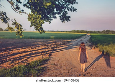 The evening sunset. Girl walks the road with her guardian angel into the field. Winged silhouette shadow. Blurred background