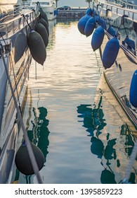 Evening, sunset, mountains, moored vessel, boards with fenders, mooring ropes. Reflection in water. Parking for ships. Europe.