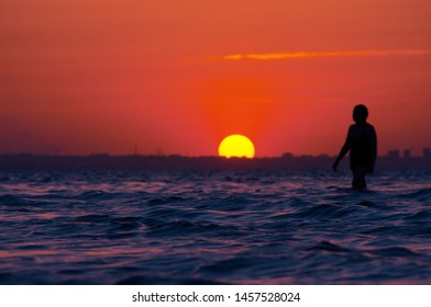 Evening. Sunset on the Mediterranean sea. the figure of a man standing in the water.