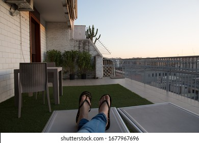 evening sunset shot of a pair of crossed female legs in jeans and feet in sandals lying, relaxing on a sun bed on a balcony with a table, chairs around and the city of Bari, Italy in the background