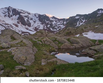 Evening sunset summer view from Bremer Hutte with lake from melting snow tongues and snow-capped moutain peaks, lush green meadow, blue sky pink refllecting clouds.