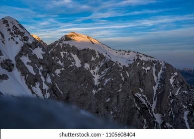 Evening and sunset view of Brana mountain, Kamnik Savinja alps, Slovenia. Stunning sunset over mountain alpine landscape with snow, rocks and summit of Brana. Blue sky, dramatic clouds.