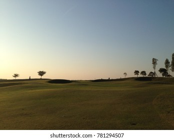 Evening sunshine with the sun on the green grass in golf course