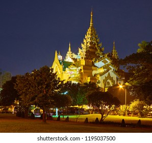 The evening Theingottara park hides the brightly illuminated West Gate of Shwedagon Zedi Daw with ornate pyatthat (multistaged) roof and leogryph (chinthe) guards at the entrance, Yangon, Myanmar.