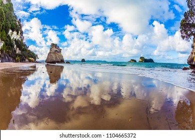 "Evening tide on the beach. The huge rock ""Sail"" and lush clouds are reflected in the smooth wet sand. Coast of the North Island of New Zealand. Concept of active and ecological tourism"