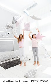 Evening time for fun. Sleepover party ideas. Sisters play pillows bedroom party. Pillow fight pajama party. Girls happy best friends or siblings in cute stylish pajamas with pillows sleepover party.
