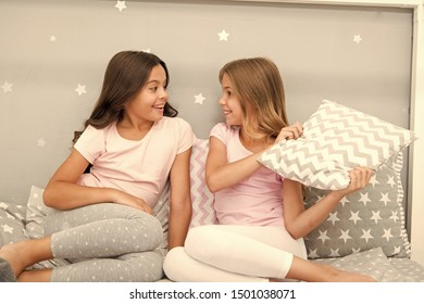 Evening time for fun. Sleepover party ideas. Girls happy best friends or siblings in cute stylish pajamas with pillows sleepover party. Sisters having fun sleepover party. Pillow fight pajama party.