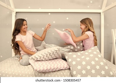 Evening time for fun. Sleepover party ideas. Girls happy best friends or siblings in cute stylish pajamas with pillows sleepover party. Sisters play pillows bedroom party. Pillow fight pajama party.