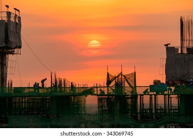 evening time of high building construction site, over time worker