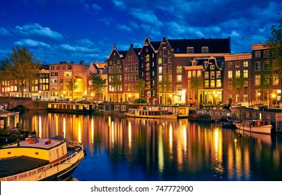 Evening town Amsterdam in Netherlands on bank river canal Amstel with shining window. Panorama landscape brown house over water reflection.